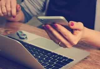 Kobieta używająca laptopa z wynajmu laptopa, trzyma w ręku telefon